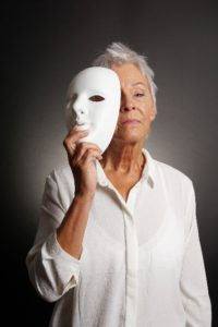 Picture shows a woman partially obscuring her face with a white mask.